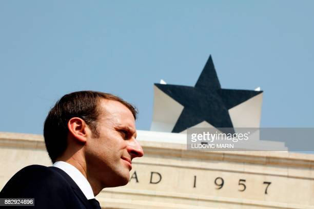 French President Emmanuel Macron listens to national anthems as he takes part in a ceremony at the Independence square in Accra on November 30 2017 /...