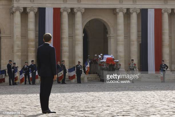 French President Emmanuel Macron looks at Legionnaires carrying the coffin during a national memorial service for Hubert Germain - the last surviving...