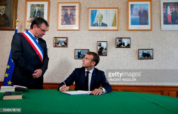 French President Emmanuel Macron looks at Mayor Pascal Babouot as he signs the guestbook at the city hall in ColombeylesDeuxEglises on October 4 2018...