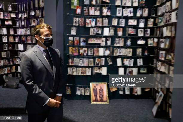 French President Emmanuel Macron looks at the images of genocide victims on display during his visit to the Kigali Genocide Memorial, where some...