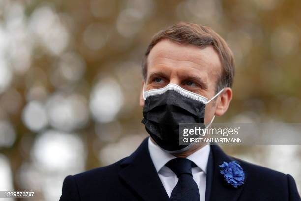 French President Emmanuel Macron looks on after laying a wreath in front of the statue of Georges Clemenceau in Paris on November 11 as part of the...
