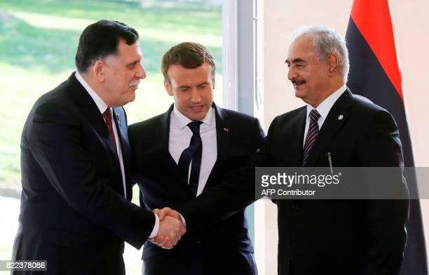 French President Emmanuel Macron looks on as Libyan Prime Minister Fayez al-Sarraj shakes hands with General Khalifa Haftar , commander in the Libyan...