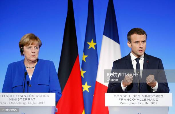 French President Emmanuel Macron makes a statement next to German Chancellor Angela Merkel during a joint press conference at the Elysee Presidential...