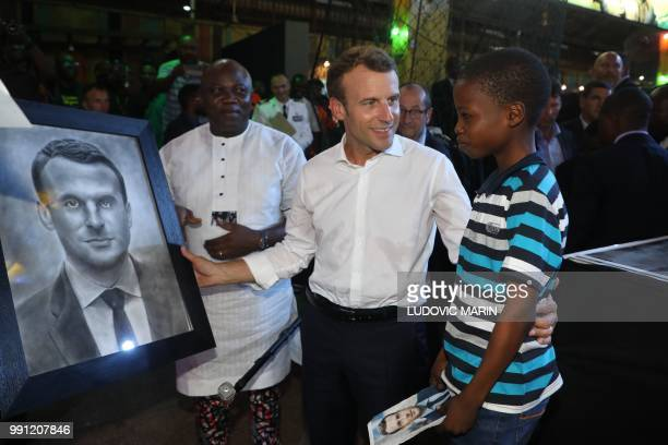 TOPSHOT French President Emmanuel Macron meets with a young boy who drew a portrait of him during a visit to the Afrika Shrine in Lagos on July 3...