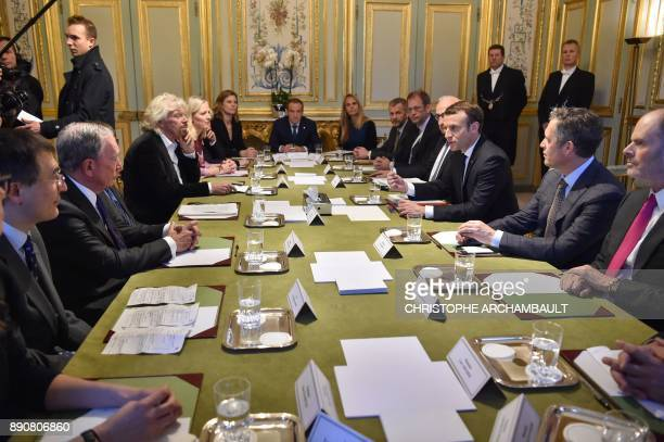 French President Emmanuel Macron meets with English investor Christopher Hohn US businessman and politician Michael Bloomberg US entrepreneur Bill...
