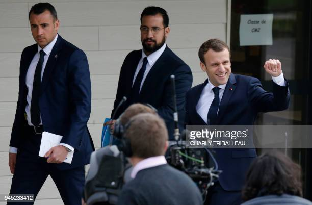 French President Emmanuel Macron next to Elysee Chief Security Officer Alexandre Benalla gestures as he arrives at a school in Berdhuis northwestern...