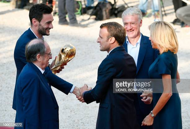 French President Emmanuel Macron next to his wife Brigitte Macron shakes hands with France's goalkeeper Hugo Lloris as France's coach Didier...
