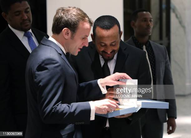 French President Emmanuel Macron offers a gift to Ethiopian Prime Minister Abiy Ahmed after a press conference on March 12 2019 in Addis Ababa