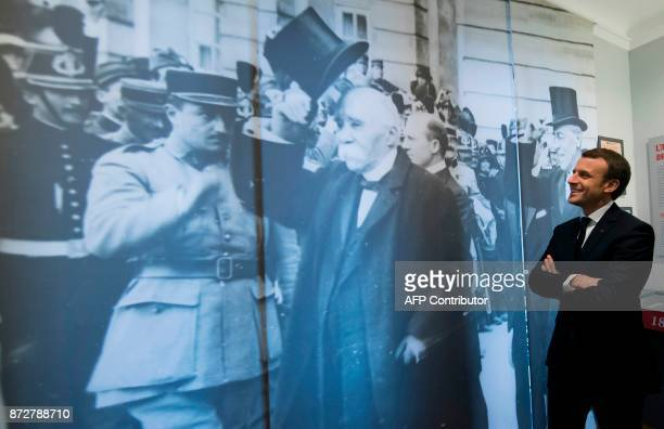 French President Emmanuel Macron passes a mural depicting former French Prime Minister during WWI Georges Clemenceau as he tours the Clemenceau...