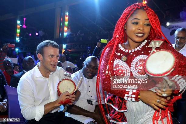 French President Emmanuel Macron plays a talking drum as he joins in at a performance at the Shrine Afrika in Lagos on July 3 2018 French President...