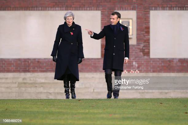 French President Emmanuel Macron points as he meets with British Prime Minister Theresa May during a wreath-laying ceremony at Thiepval Memorial on...