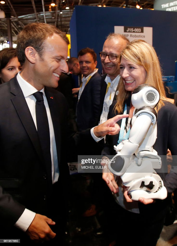 TOPSHOT - French President Emmanuel Macron points to a robot at the VivaTech gadget show ( (Viva Technology) in Paris on May 24, 2018. - Macron urged Facebook CEO and the bosses of other tech companies accused of hoovering up personal data while avoiding taxes to use their clout for global good. Around 60 industry leaders travelled to Paris for talks with the French leader about improving the lives of workers in the gig economy and being better corporate citizens generally.