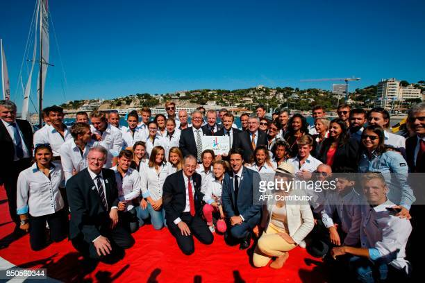 French President Emmanuel Macron poses for a family photo standing with International Olympic Committee President Thomas Bach members of the French...