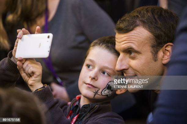 TOPSHOT French President Emmanuel Macron poses for a selfie picture with a child during a Christmas ceremony for children on December 13 at the...