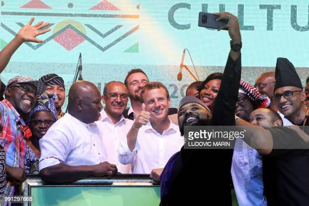 French President Emmanuel Macron poses for a selfie with Nigerian artists Femi Kuti Youssou N'Dour and Angelique Kidjo at the Shrine Afrika in Lagos...