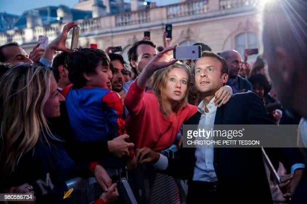 French president Emmanuel Macron poses for pictures with people during the annual 'Fete de la Musique' in the courtyard of the Elysee Palace in Paris...