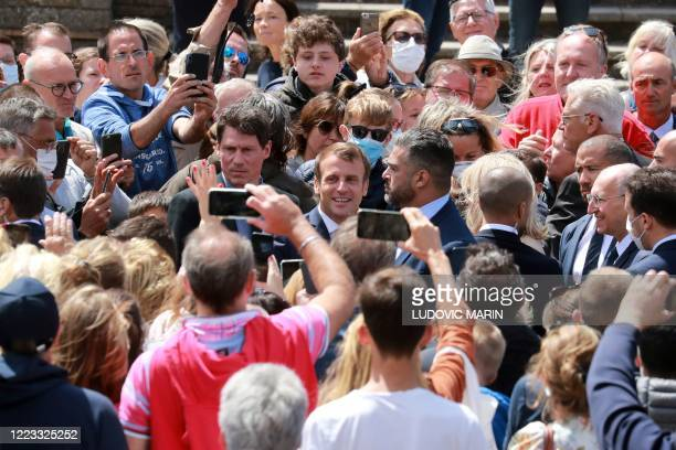 French president Emmanuel Macron poses for wellwishers as he leaves the city hall, after voting for the second round of the mayoral elections on June...
