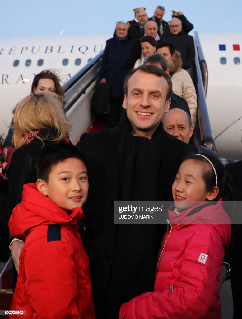 French President Emmanuel Macron (C) poses on the tarmac with children upon his arrival at Beijing's Capital Airport on January 8, 2018. French President Emmanuel Macron urged Europe on January 8 to take part in China's massive Silk Road infrastructure project but warned against 'hegemony', saying both sides should share the benefits. / AFP PHOTO / POOL / Ludovic MARIN