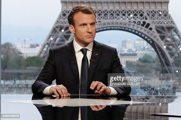 TOPSHOT French President Emmanuel Macron poses on the TV set before an interview with RMCBFM and Mediapart French journalists at the Theatre national...