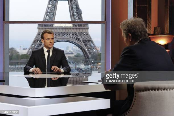 French President Emmanuel Macron poses on the TV set before an interview with RMCBFM French journalist JeanJacques Bourdin and Mediapart...