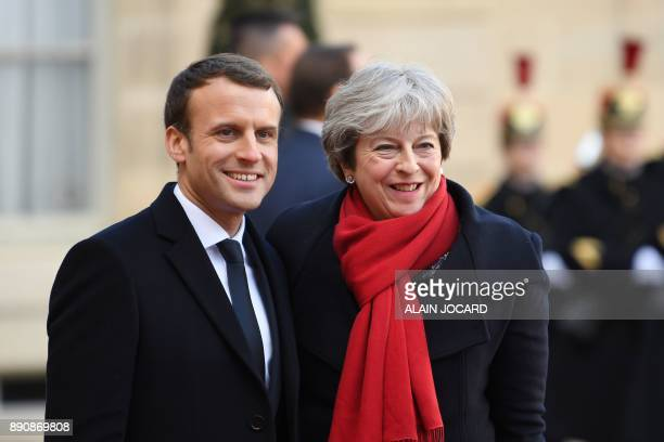 French President Emmanuel Macron poses with Britain's Prime Minister Theresa May as she arrives at the Elysee palace on December 12 2017 in Paris for...