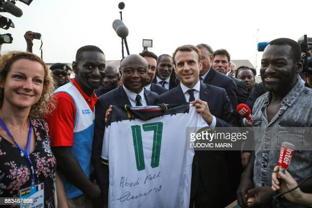 French President Emmanuel Macron poses with former Ghanaian football player Abedi Pele within a meeting with young members of a female football club...