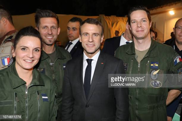 French President Emmanuel Macron poses with French soldiers from the Barkhane force during a dinner at the Barkhane tactical command center in...