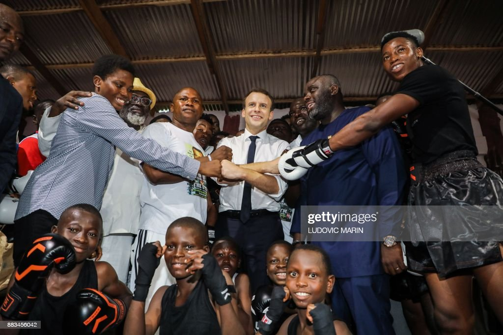 TOPSHOT - French President Emmanuel Macron (C) poses with youmg members during a visit to The Gym boxing club in the Jamestown quarter on November 30, 2017 in Accra. /