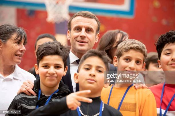 French President Emmanuel Macron, poses with youths during his visit in Mulhouse during a trip on the theme of the republican reconquest and the...