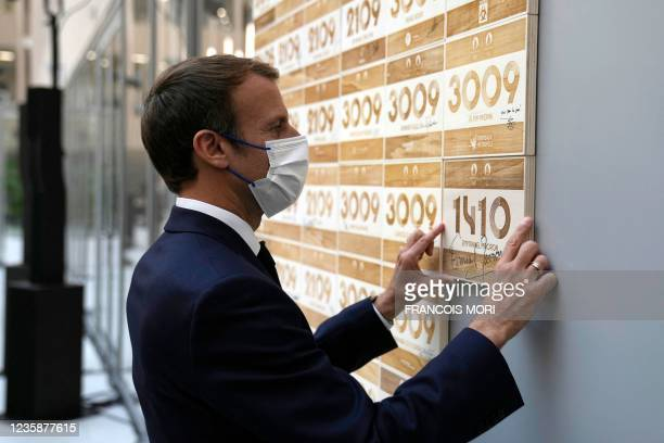 French President Emmanuel Macron puts his signed plaque to mark his visit to the headquarters of the Paris 2024 Organising Committee for the Olympic...