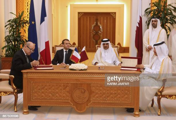 French President Emmanuel Macron Qatari Emir Sheikh Tamim bin Hamad alThani watch French Foreign Minister JeanYves Le Drian and his Qatari...