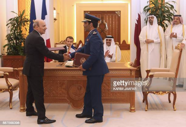 French President Emmanuel Macron Qatari Emir Sheikh Tamim bin Hamad alThani applaud as Eric Trappier the director general of Dassault Aviation and...