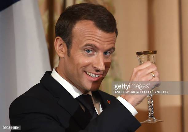 French President Emmanuel Macron raises his glass after a toast during a luncheon at the US State Department in Washington DC on April 24 2018