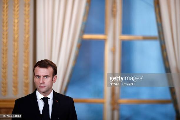 French President Emmanuel Macron reacts during a joint press conference with President of Burkina Faso at the Elysee Palace in Paris, on December 17...