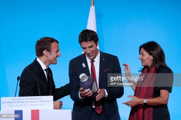 French President Emmanuel Macron reacts on the podium with Executive President of the Paris delegation Tony Estanguet and Mayor of Paris Anne Hidalgo...