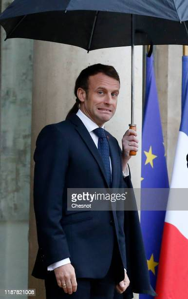 French President Emmanuel Macron reacts to the pouring rain as he awaits the arrival of the European Council President-elect Charles Michel prior to...