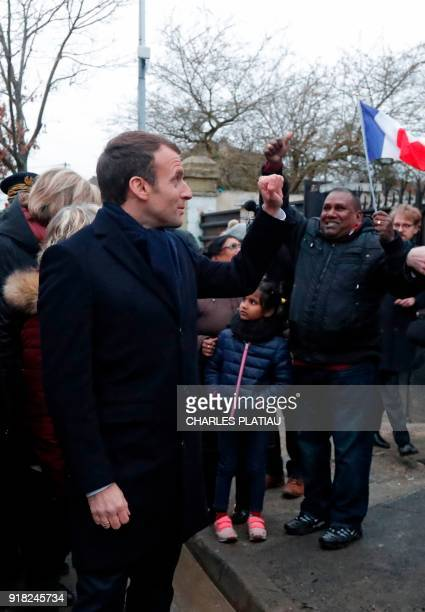 French President Emmanuel Macron reacts with residents one waving a French flag during a visit to a neighborhood that suffered from flooding after...