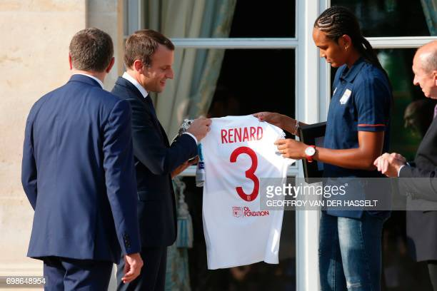 French President Emmanuel Macron received a jersey by Lyon's French captain Wendie Renard during a ceremony at the Elysee Palace in Paris on June 20...