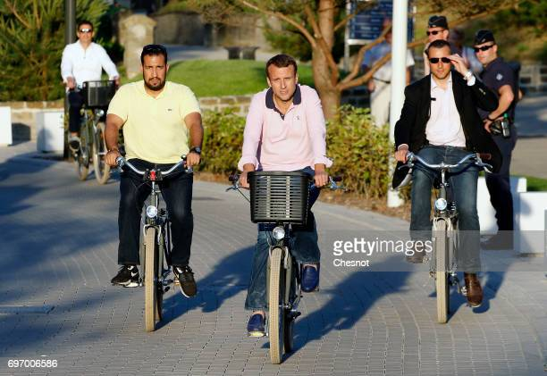 French President Emmanuel Macron returns to his house on a bicycle with his deputy chief of staff Alexandre Benalla on the eve of the second round of...
