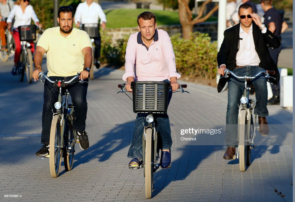 French President Emmanuel Macron returns to his house on a bicycle with his deputy chief of staff Alexandre Benalla (L) on the eve of the second round of the French parliamentary elections on June 17, 2017 in Le Touquet-Paris-Plage, France. The second round of the French legislative elections will take place on June 18, 2017.