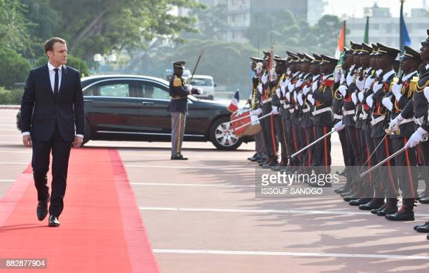 French President Emmanuel Macron reviews an honour guard beffore a meeting with Ivory Coast's President at the Presidential Palace in Abidjan on...