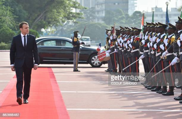 French President Emmanuel Macron reviews an honour guard before a meeting with Ivory Coast's President at the Presidential Palace in Abidjan on...
