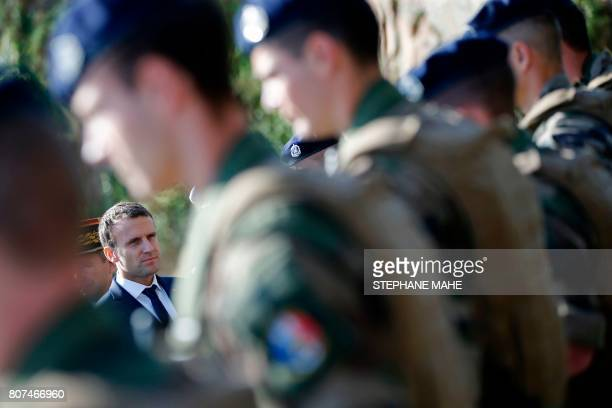 French President Emmanuel Macron reviews troops during a visit to the Ile Longue Defence unit a submarine navy base in Crozon near Brest western...