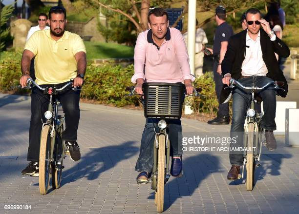 TOPSHOT French President Emmanuel Macron rides a bicycle in the streets of Le Touquet northern France on June 17 accompanied by Elysee senior...