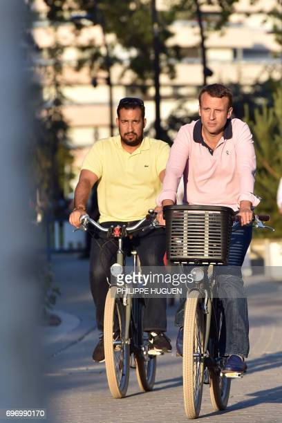 French President Emmanuel Macron rides a bicycle with Elysee senior security officer Alexandre Benalla in the streets of Le Touquet northern France...