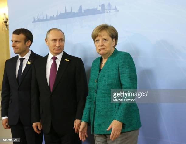 French President Emmanuel Macron Russian President Vladimir Putin and German Chancellor Angela Merkel pose for a photo during their meeting to talk...