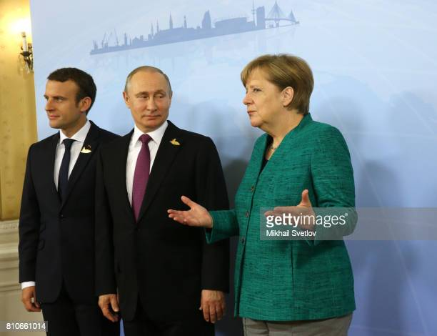 French President Emmanuel Macron Russian President Vladimir Putin and German Chancellor Angela Merkel pose for a photo during their meeting to talk...