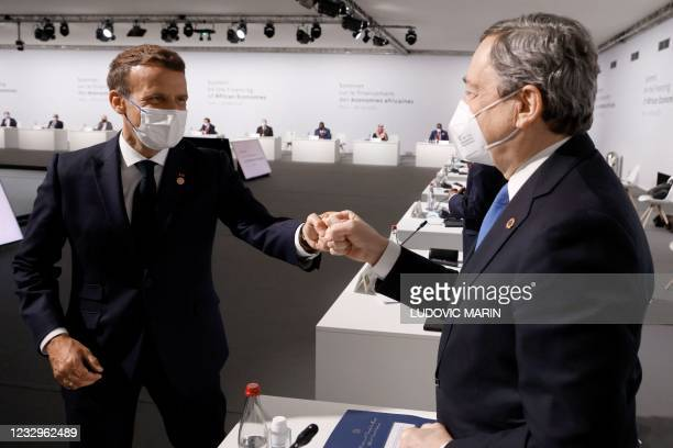 French President Emmanuel Macron salutes Italy's Prime Minister Mario Draghi before the opening session of the Summit on the Financing of African...