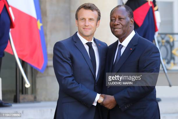 French President Emmanuel Macron salutes Ivory Coast's President Alassane Ouattara as he leaves following a meeting with French President at the...