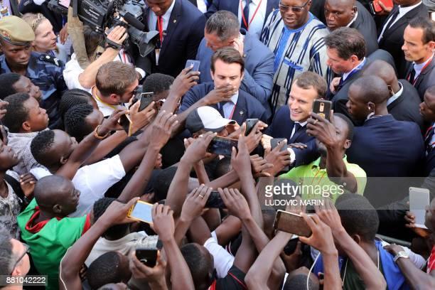 French President Emmanuel Macron salutes residents as he leaves the Ouagadougou University after giving a speech on November 28 in Ouagadougou as...